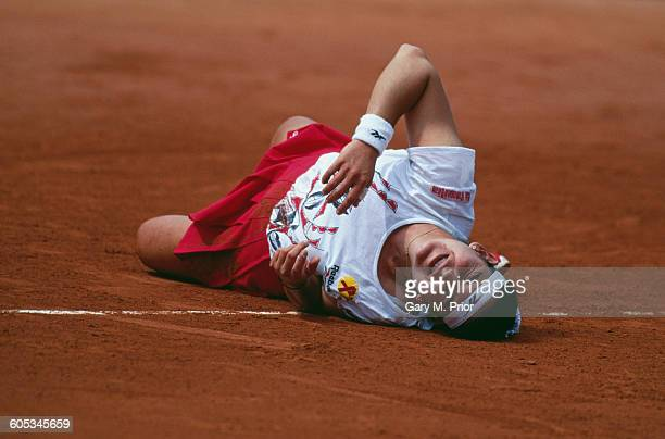 Arantxa Sanchez Vicario of Spain rolls on the ground in pain after she injures her wrist during the Women's Singles Fourth Round match against Anke...