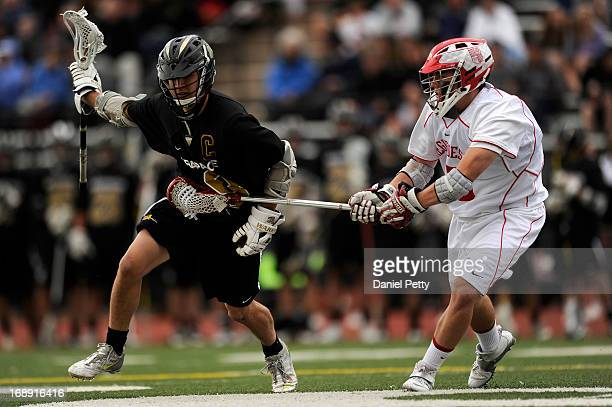 Arapahoe High School senior midfielder Ben Eigner left carries the ball while defended by Regis Jesuit freshman defenseman Ian Desmond during a CHSAA...
