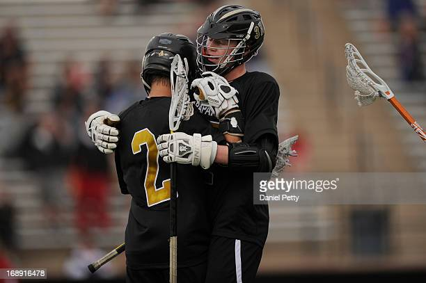 Arapahoe High School senior midfielder Michael Babb celebrates after a goal with junior attacker Brendan Till during a CHSAA 5A boys lacrosse...