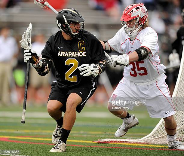 Arapahoe High School senior midfielder Michael Babb dodges Regis Jesuit senior defenseman Brian Wegner during the first quarter of a CHSAA 5A boys...