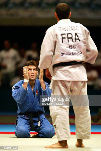 Arash Miresmaili of Iran gestures as he thanks to the god after winning over French Larbi Benboudaoud by ippon during the men's under 66 kg class...