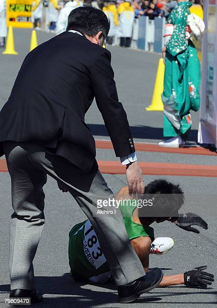 Arata Fujiwara of Japan falls to the crowd after crossing the finish line in second place during the 2008 Tokyo Marathon at Tokyo Big Sight on...