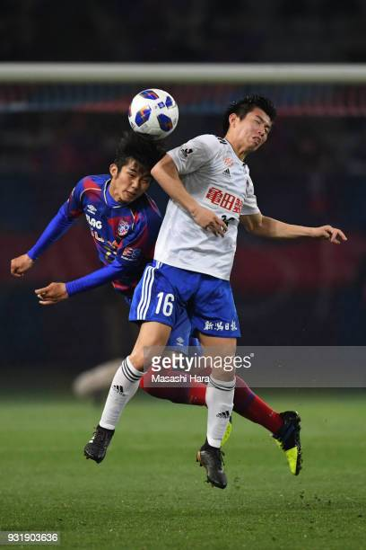 Arata Watanabe of Albirex Niigata and Makoto Okazaki of FC Tokyo compete for the ball during the JLeague YBC Levain Cup Group A match between FC...