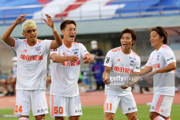 Arata Watanabe of Albirex Niigata celebrates scoring his side's first goal with his team mates during the J.League Meiji Yasuda J2 match between...