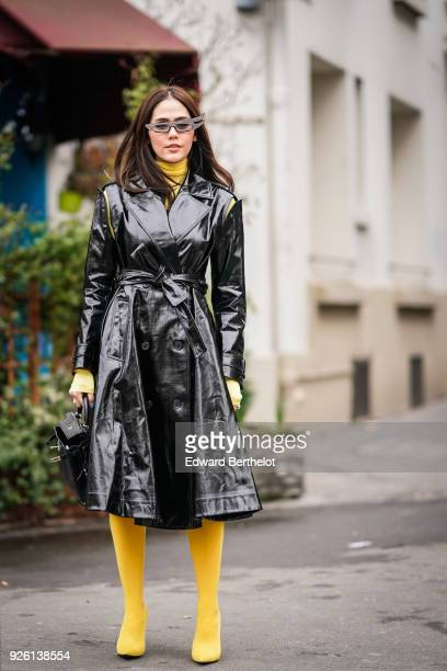 Araya Hargate wears a black leather trench coat yellow boots sunglasses during Paris Fashion Week Womenswear Fall/Winter 2018/2019 on March 1 2018 in...