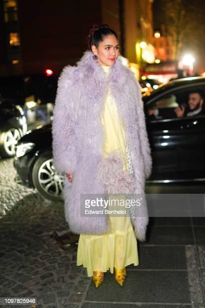 Araya Hargate wears a pale purple faux fur coat a yellow dress earrings outside Valli during Paris Fashion Week Haute Couture Spring Summer 2020 on...