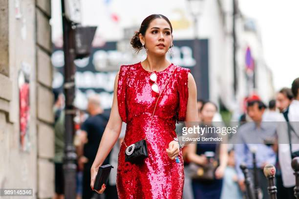 Araya Hargate wears a red shiny glitter dress a black bag outside Givenchy during Paris Fashion Week Haute Couture Fall Winter 2018/2019 on July 1...
