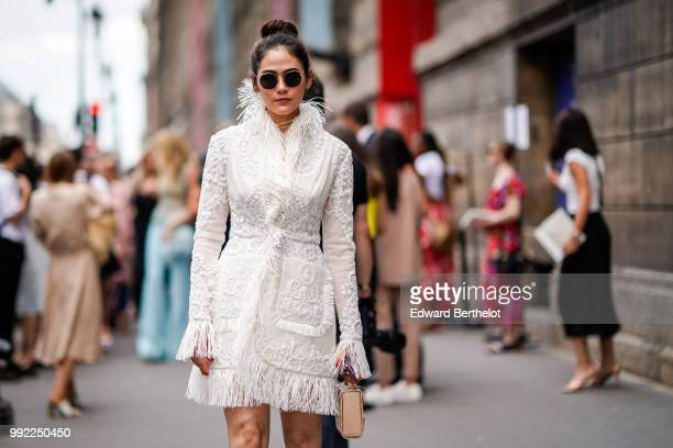 Araya Hargate wears a white dress with faux fur and embroidered features outside Elie Saab during Paris Fashion Week Haute Couture Fall Winter...