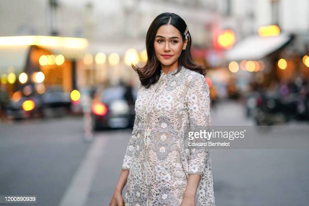 Araya Hargate wears hair clips, earrings, a white lace dress , outside Ralph & Russo, during Paris Fashion Week - Haute Couture Spring/Summer 2020,...