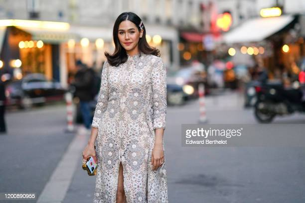 Araya Hargate wears hair clips earrings a white lace frontsplit dress a goldtone and colorful minaudiere outside Ralph Russo during Paris Fashion...