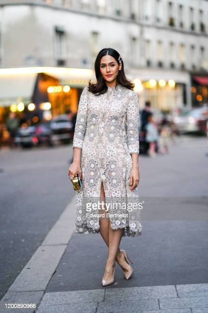 Araya Hargate wears hair clips, earrings, a white lace front-split dress, nude-color pointy heeled pumps, a gold-tone and colorful minaudiere ,...