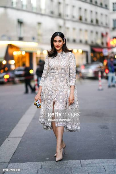 Araya Hargate wears hair clips earrings a white lace frontsplit dress nudecolor pointy heeled pumps a goldtone and colorful minaudiere outside Ralph...