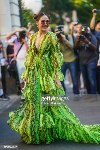 Araya Hargate wears sunglasses a green snake print ruffled dress earrings a white bag outside Giambattista Valli during Paris Fashion Week Haute...