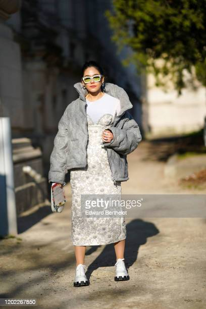 Araya Hargate wears white sunglasses gray winter oversized puffer jacket a white tshirt a bejeweled dress with embroidery earrings white shoes a...