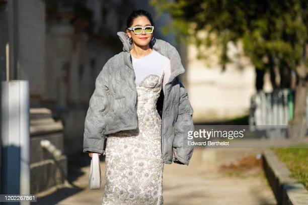 Araya Hargate wears white sunglasses gray winter oversized puffer jacket a white tshirt a bejeweled dress with embroidery earrings outside Elie Saab...