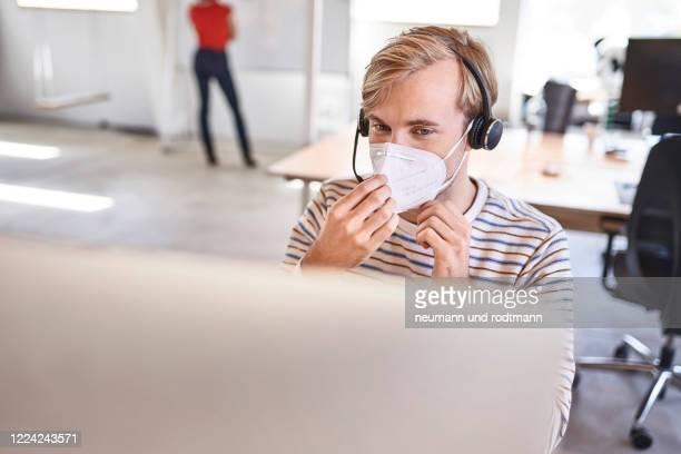 arbeiten im büro mit maske - coronavirus mit stock pictures, royalty-free photos & images