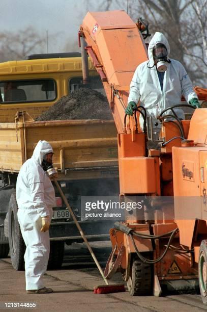 Arbeiter einer Straßenbaufirma schleifen am 28. Februar 1993 mit Gasmasken und Schutzanzügen bekleidet einen Teil der Uferstraße im Frankfurter...