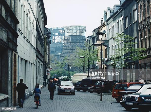 Arbeiterviertel DuisburgRuhrort Blick in eine verkehrsberuhigte gepflasterte Straße deren Anblick von rußigen Fassaden parkenden Autos und dem zarten...