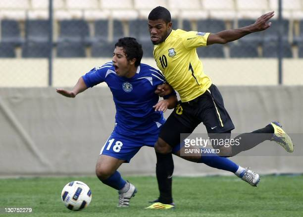 Arbil's Club's player Muslem Mubarak vies for the ball against AlTalaba Club's Muhammed Faisal during the opening match of the Iraqi League football...