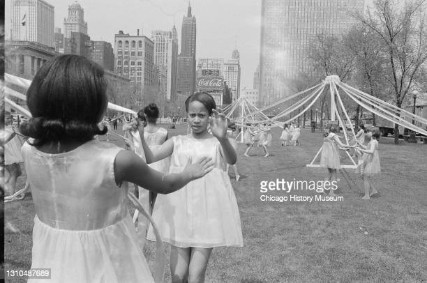 Arbor Day festivities, Mayor Richard J Daley speaks and helps plant a crabapple tree with wife Sis Daley, children dance around maypole, and choir...