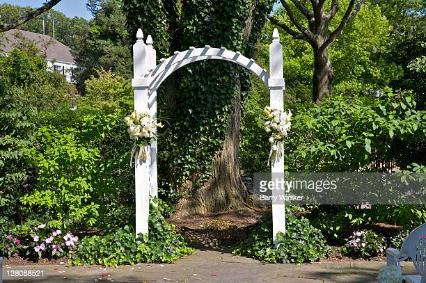 Arbor with flowers for wedding in front of old tree with ivy, Stony Brook, NY, U.S.A.