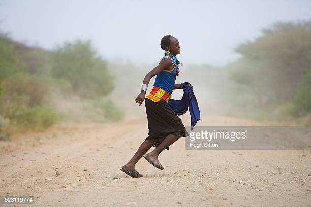 arbore woman running across road - hugh sitton ethiopia stock pictures, royalty-free photos & images