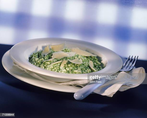 Arborio rice with pamesan cheese on plate with fork