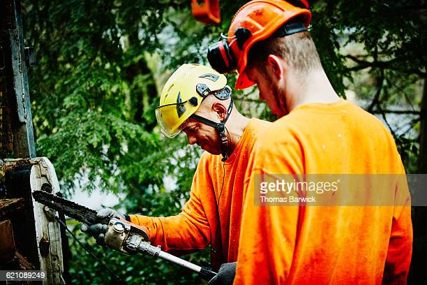 Arborist attaching saw to pole trimmer