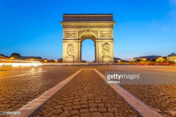 arc de triomphe at dusk,paris - arc de triomphe photos et images de collection