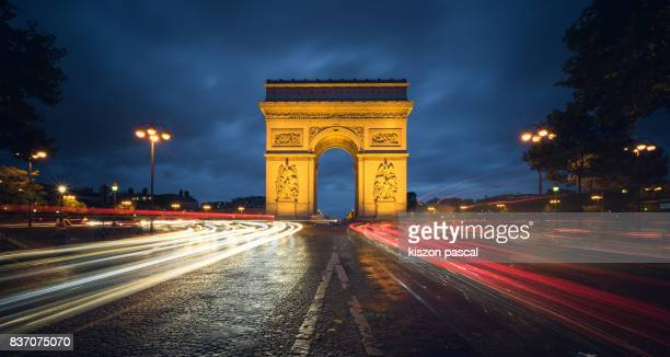 arc de triomphe in Paris at night with traffic ( France )