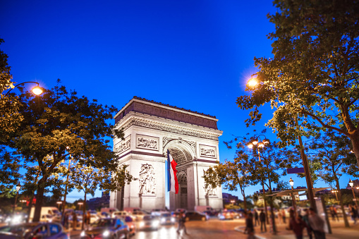 Arc de Triomphe in Paris with a big French flag under it 914965638