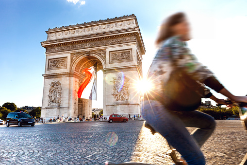 Arc de Triomphe in Paris with a big French flag under it 915690060