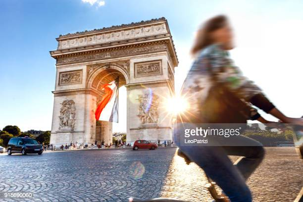 arc de triomphe in paris with a big french flag under it - champs elysees quarter stock pictures, royalty-free photos & images