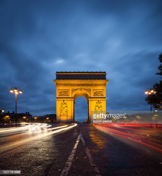arc de triomphe monument with light trail of cars in paris during night , france - triumphal arch stock photos and pictures