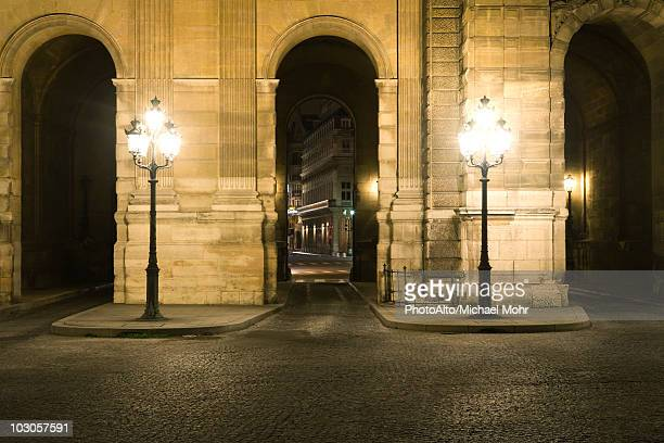 arcade illuminated by street lamps, the louvre, paris, france - louvre photos et images de collection