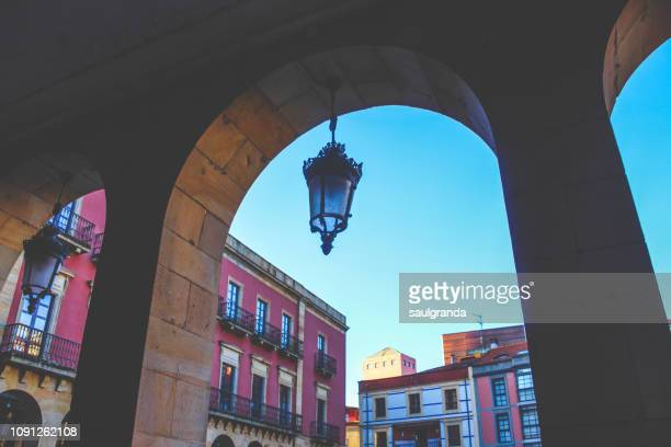 arcade of stone with a street light and houses in the background - gijon fotografías e imágenes de stock
