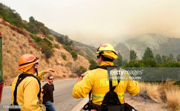 Arcadia resident Mark Zeldin speaks with firefighters keeping an eye on the Bobcat Fire as it burns on a hillside behind homes in Arcadia, California...