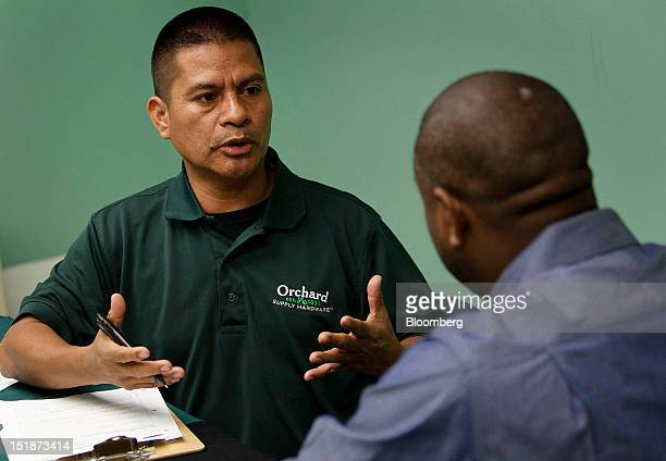 Arcadio Cruz, left, interviews a job applicant during a hiring fair for the renovated West Los Angeles Orchard Supply Hardware store at the Midtown...