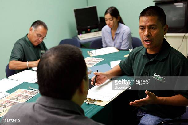 Arcadio Cruz, right, interviews a job applicant during a hiring fair for the renovated West Los Angeles Orchard Supply Hardware store at the Midtown...