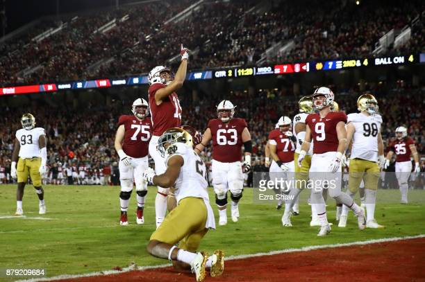 ArcegaWhiteside of the Stanford Cardinal celebrates after catching a touchdown pass while covered by Julian Love of the Notre Dame Fighting Irish at...