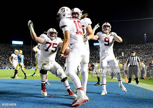 ArcegaWhiteside of the Stanford Cardinal celebrates his touchdown with Daniel Marx and AT Hall and Dalton Schultz to take the lead over the UCLA...