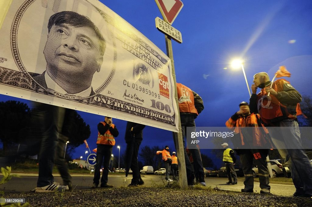 ArcelorMittal's workers demonstrate in front of a giant fake 100-us-dollar banknote with a portrait of Lakshmi Mittal at the entrance of the plant of Basse-Indre on December 10, 2012 in Indre, western France, to protest against the transfer of a part of their activity to the group's plant in Florange.