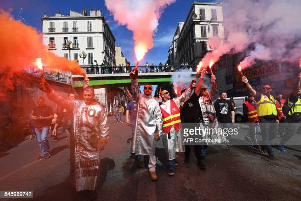 ArcelorMittal's workers hold flares during a protest called by several French unions against the labour law reform in Marseille southern France on...