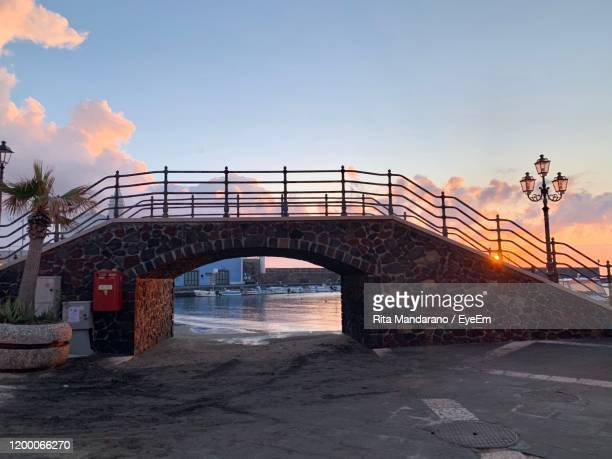 arch bridge against sky during sunset - isole eolie foto e immagini stock