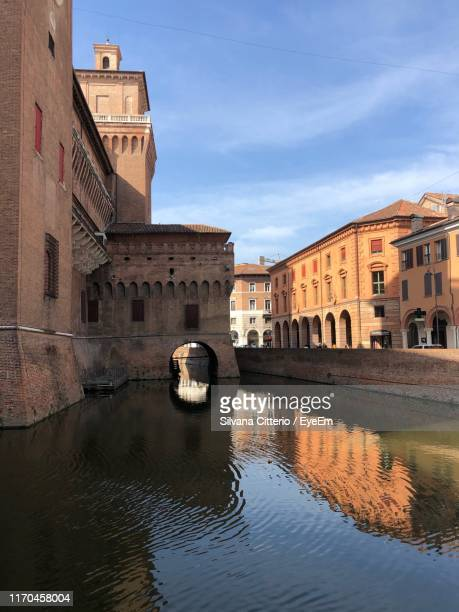 arch bridge over canal amidst buildings in city against sky - ferrara stock pictures, royalty-free photos & images