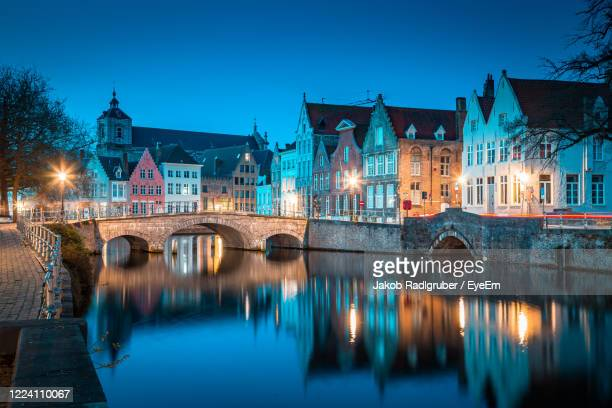 arch bridge over canal by buildings in town - belgium stock pictures, royalty-free photos & images