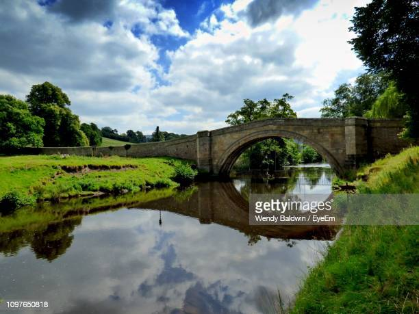 arch bridge over lake against sky - chatsworth derbyshire stock pictures, royalty-free photos & images