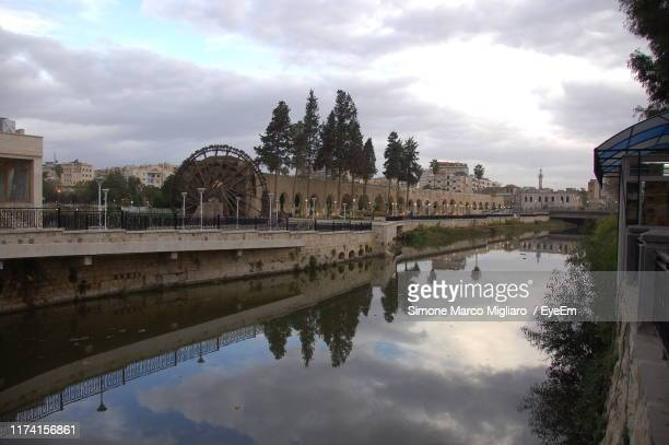 arch bridge over lake against sky - syria stock pictures, royalty-free photos & images