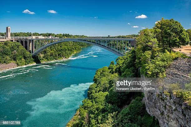 arch bridge over niagara river against blue sky - niagara river stock pictures, royalty-free photos & images