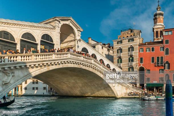 arch bridge over river against buildings in city - veneto stock pictures, royalty-free photos & images